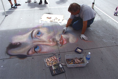 Chalk artist drawing realistic face onto street