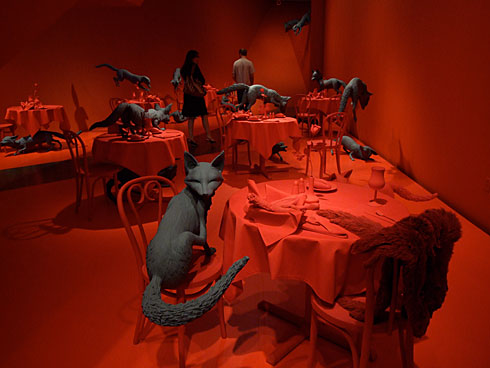 The red tables and grey foxes of Fox Games by Sandy Skoglund