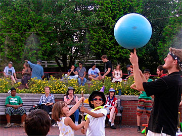 Juggler showing kids how to spin a blue ball on a stick