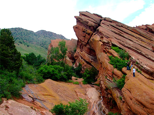 People atop a huge red sandstone formation