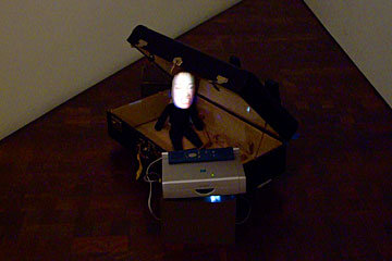 Tiny doll in a suitcase, Zero by Tony Oursler