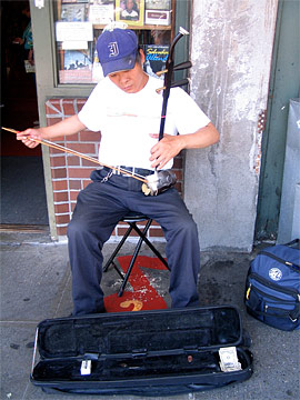 Chinese man playing strange instrument on the street