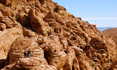 People standing on ancient red boulders along ridge