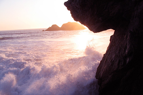 Sunset behind wave crashing onto beach rocks