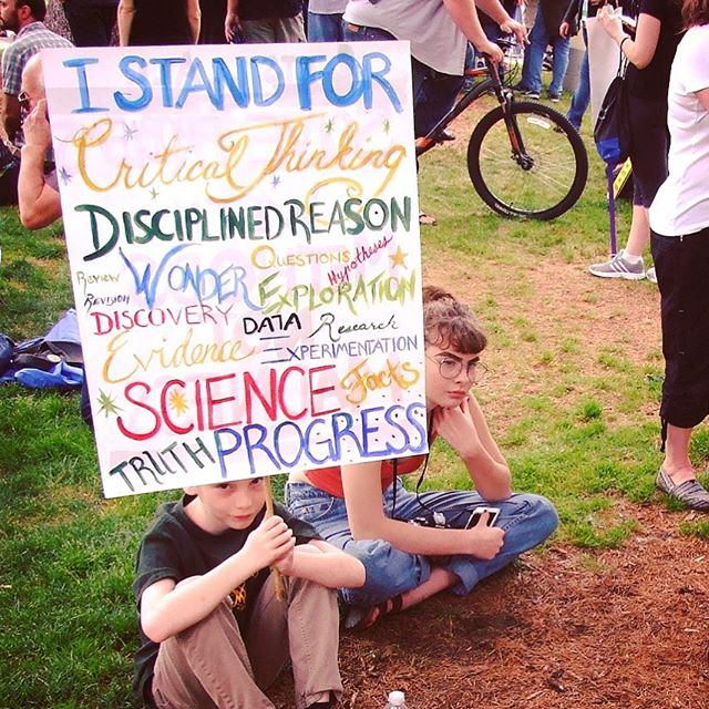Kids holding I Stand For Critical Thinking sign at March for Science