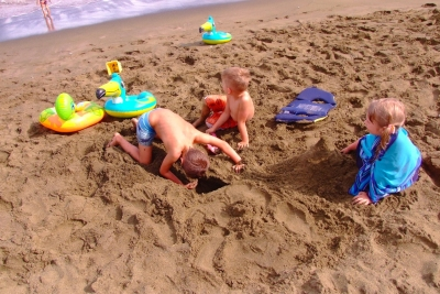Kids playing in Mahana Bay green sand